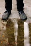 Les pieds et les jambes d'un homme se sont reflétés dans un magma sur la rue. Photo libre de droits