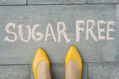 Les pieds femelles avec du sucre des textes libèrent écrit sur le trottoir gris photo libre de droits
