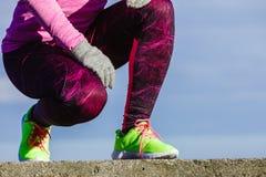 Les pieds femelles de jambes dans la couleur vive jaunissent des chaussures sur le bord de la mer Photographie stock
