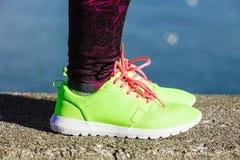 Les pieds femelles de jambes dans la couleur vive jaunissent des chaussures sur le bord de la mer Images stock