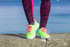 Les pieds femelles de jambes dans la couleur vive jaunissent des chaussures sur le bord de la mer Photos libres de droits