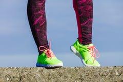 Les pieds femelles de jambes dans la couleur vive jaunissent des chaussures sur le bord de la mer Image stock