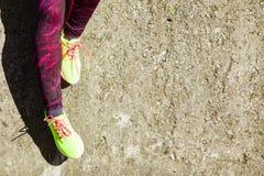 Les pieds femelles de jambes dans la couleur vive jaunissent des chaussures sur le bord de la mer Image libre de droits