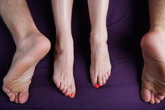 Les pieds femelles et masculins se trouvent sur une feuille violette Les amants ont le sexe Images libres de droits