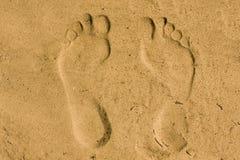 Les pieds impriment en sable Photos stock