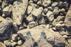 Les pieds masculins dans des chaussures de toile se tiennent sur des roches Photographie stock libre de droits