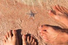 Les pieds masculins et femelles se tiennent sur le sable coquillier Image stock