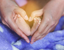Les pieds nouveau-nés de bébé dans la mère remet en forme de coeur Photos stock