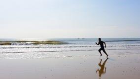 Les pieds nus équipent le fonctionnement sur la plage avec des vagues Photos stock