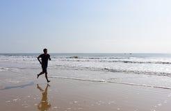 Les pieds nus équipent le fonctionnement sur la plage avec des vagues Images libres de droits