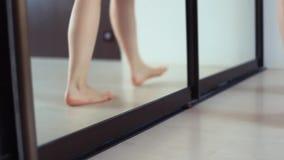 Les pieds nus de la femme ouvre la porte de tiroir de miroir dans le salon d'appartement clips vidéos