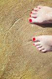 Les pieds pedicured de la femme avec le vernis à ongles rouge sur des orteils dans le sable dans l'eau image stock