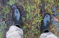 Les pieds sont dans les genou-bottes en caoutchouc Images stock