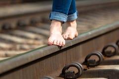 Les pieds sont sur le plan rapproché de chemin de fer Photographie stock