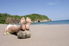 Les pieds tropicaux menteur de plage de Madame ont augmenté sur la noix de coco Photographie stock libre de droits