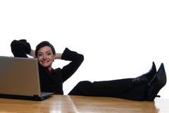 Les pieds vers le haut sur le bureau, facile le fait - regarder l'appareil-photo Image stock