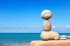 Les pierres blanches équilibrent sur un fond de ciel bleu et de mer Photos stock