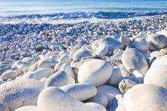 Les pierres blanches et grises ont doucement arrondi et ont délogé de l'eau de mer photo libre de droits