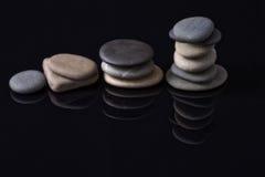 Les pierres de mer étendues dans les piles se sont reflétées outre du noir Photographie stock