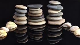 Les pierres de mer étendues dans les piles se sont reflétées outre du noir images libres de droits