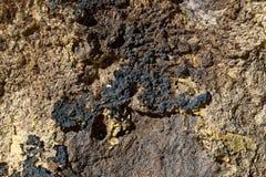 Les pierres et le mur en béton avec la tache jaune de peinture et un trou textotent Image libre de droits