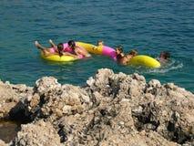 Les pierres, familles sur la plage joue en mer Image stock