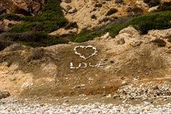 Les pierres ont inscrit le mot de ` d'amour de ` avec un grand coeur sur une plage chez Aphrodite Rock en Chypre Images libres de droits