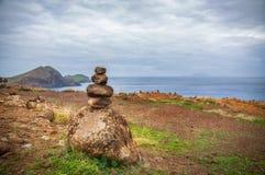 Les pierres rugueuses dans l'équilibre sur l'océan étayent Images stock