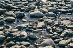 Les pierres se situent dans l'eau avec des réflexions de lumière du soleil Photographie stock libre de droits