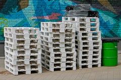 Les piles de palettes en bois blanches et de métal vert barrel Image stock