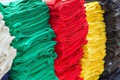 Les piles des vêtements colorés sur un marché calent Image libre de droits