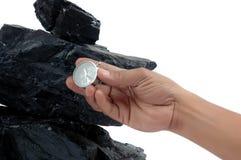 Les piles du charbon et d'un compas se sont retenues par les hommes Photo libre de droits