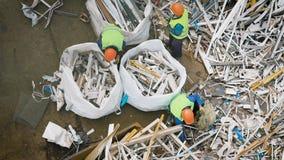Les piles mises de travailleurs industriels des déchets métalliques dans des sacs pour l'avenir réutilisent banque de vidéos