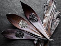 Les piles noires, blanches et parfumées des poivrons dans la feuille sèche dirige o images stock