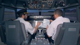 Les pilotes ont lu un manuel dans un habitacle d'un simulateur de vol 4K clips vidéos