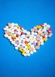 Les pilules à un coeur forment sur un bleu photos libres de droits