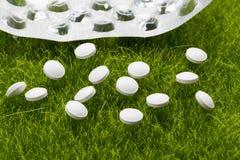 Les pilules antibiotiques blanches et le habillage transparent vide ont dispersé sur l'herbe images stock