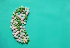 Les pilules de médecine marque sur tablette des capsules dans la forme du rein humain à l'arrière-plan bleu avec l'espace pour le photographie stock libre de droits