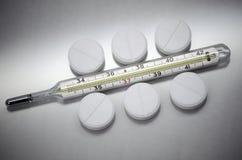 Les pilules se trouvent ? c?t? du thermom?tre m?dical images stock