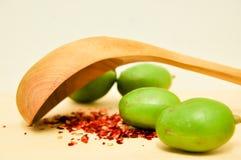 Les piments rouges s'écaillent avec une cuillère en bois faisant face vers le bas Image stock