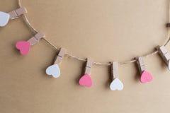 Les pinces à linge avec des coeurs sont bloc-notes Papier bleu de fond Photos stock