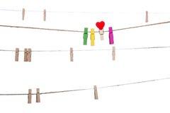 Les pinces à linge colorées avec la forme de coeur coupent sur une corde à linge Images libres de droits