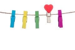 Les pinces à linge colorées avec la forme de coeur coupent sur une corde à linge Photos stock