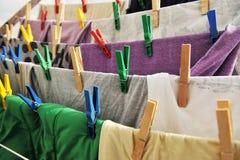 Les pinces à linge colorées tiennent les vêtements sur une corde Photos stock