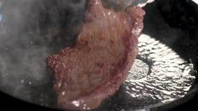 Les pinces de chef tournent le bifteck sur une casserole chaude a fait frire l'apetite, avec une croûte de viande Pr?paration de  clips vidéos