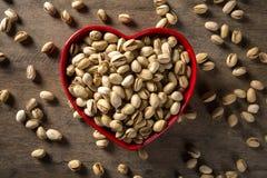 Les pistaches au coeur roulent avec le fond en bois Photographie stock