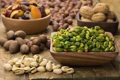 Les pistaches ont ?pluch? vert dans la cuvette en bois sur la table, style grunge photo libre de droits