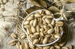 Les pistaches ont fait frire avec du sel dans la tasse blanche sur le plateau rond de paille Photo stock