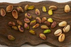Les pistaches se ferment sur un conseil en bois image stock