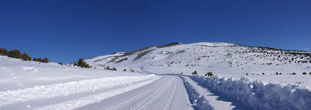 Les pistes sur la neige ont couvert la route Photos stock